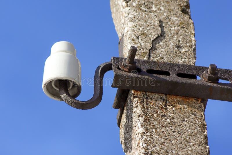 En gammalmodig omodern keramisk isolator som monteras på en gammal skadad konkret stolpe arkivfoton