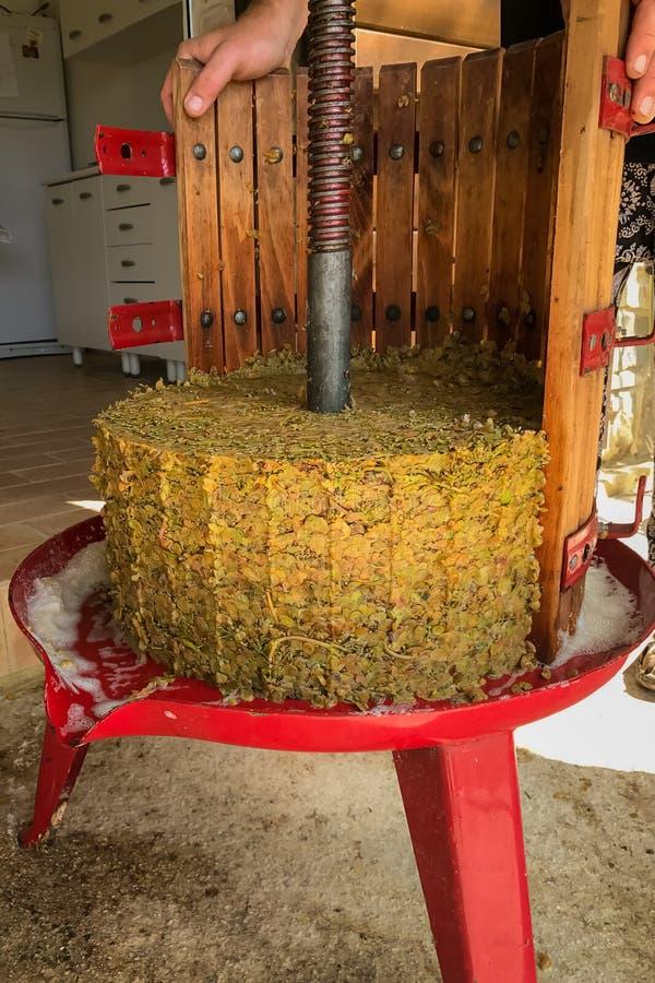 En gammalmodig trätrumma formade druvapress med sidan som togs bort och trämassan från de pressande druvorna royaltyfri foto