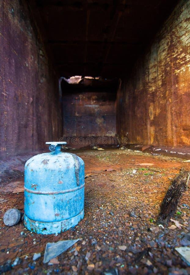 En gasbehållare sitter inom en gammal rostig dumpster arkivbild