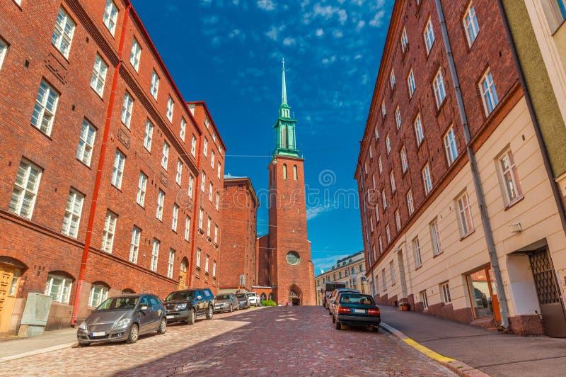En gata av Helsingfors med den traditionella arkitekturen och en kyrka Kristuskyrkan, i den finlandssvenska neo-gotiska stilen arkivbilder