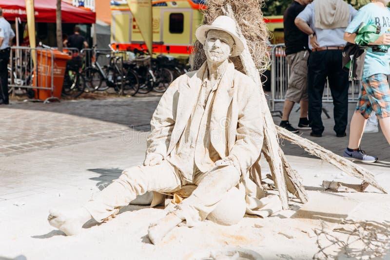 En gatakonstnär utför den täckte bosatta statyn med torkad gyttja, som, om den var i en öken Muenster Tyskland royaltyfri fotografi