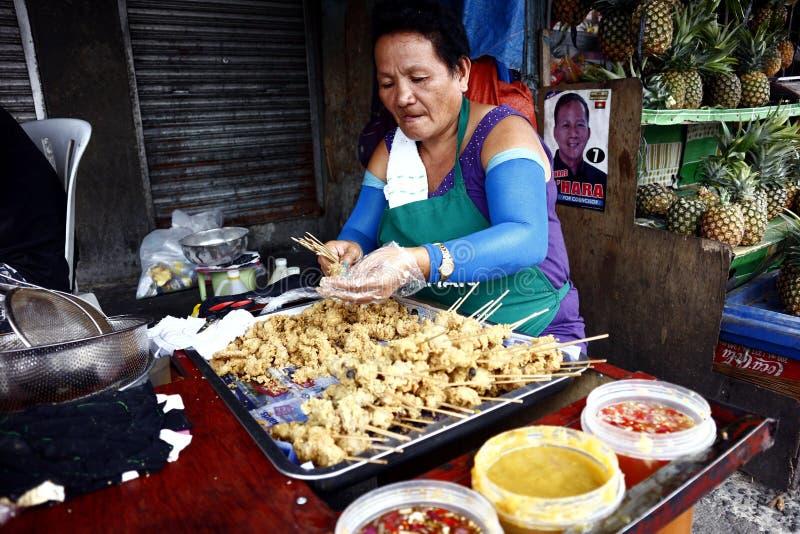 En gatamatförsäljare sätter den djupa stekt kycklinginälvan in i grillfestpinnar royaltyfri bild