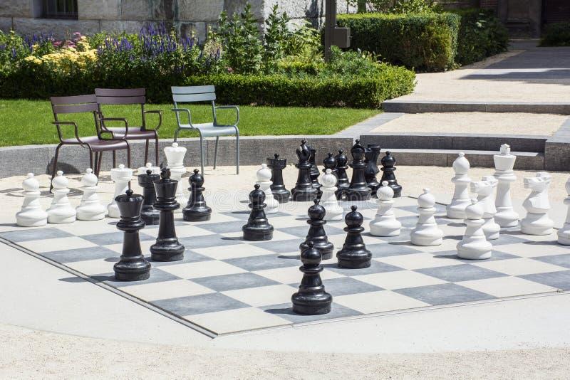 En gataschackbräde med svartvita schackpjäser, stolar och gröna växter i dagsljuset royaltyfri foto