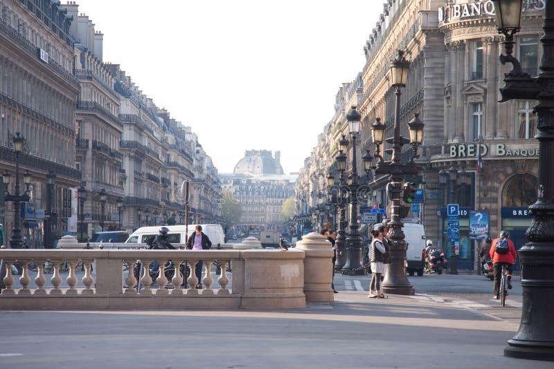 En gatasikt av avenyn de l `-opera med den Solfea banken på rätten och Hotell du Louvre Hyatt i bakgrunden arkivbild