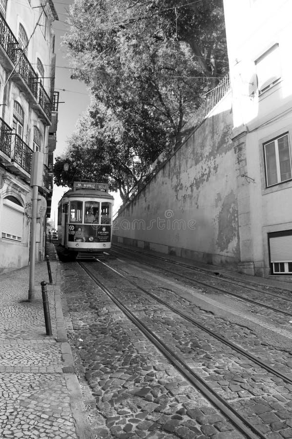 En gatasikt av det historiska arkitektoniska området Alfama med en rörande spårvagn i Lissabon, Portugal royaltyfri foto