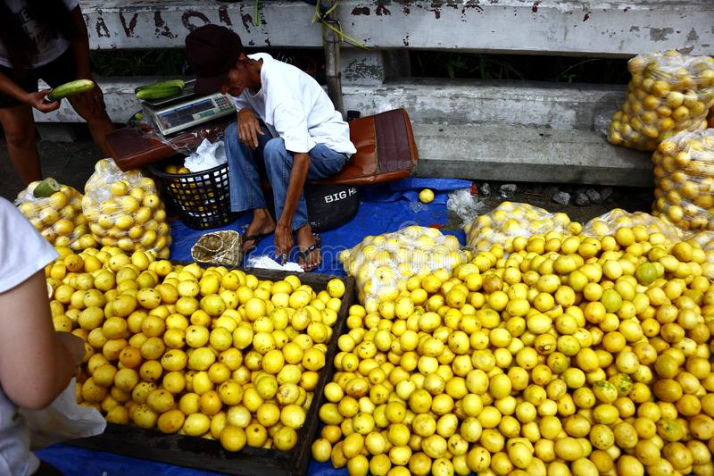 En gatuförsäljare säljer den nya och mogna citronen på en trottoar längs en huvudväg arkivbild