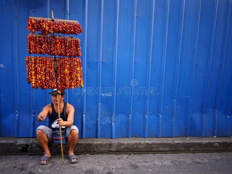 En gatuförsäljare säljer färgrika girlander av torkade eviga blommor arkivfoto