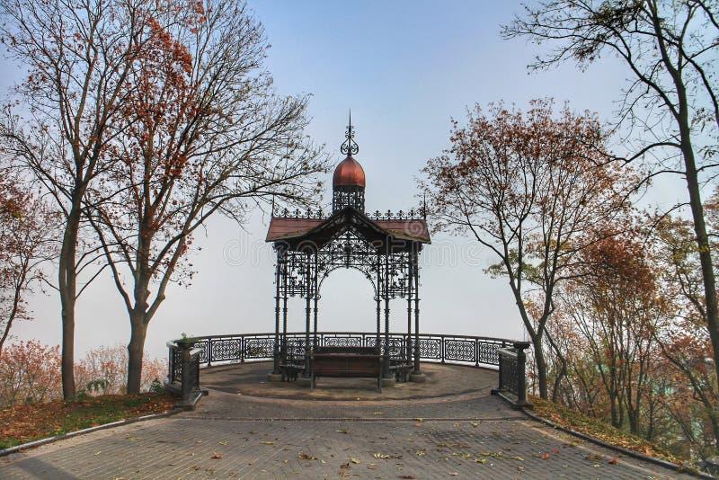 En gazebo på en mistdag på hösten i nationalparken Volodymyrska i Kiev, Ukraina royaltyfri fotografi