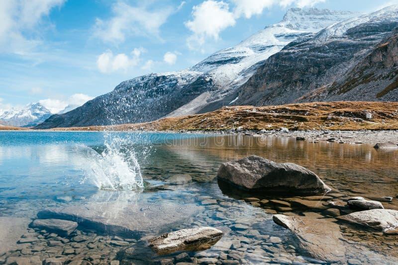 En genomskinlig bergsjö med stenar och stänker royaltyfria foton