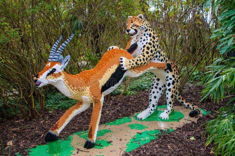 En gepard som jagar en antilopstaty som göras från Lego tegelstenar arkivbild