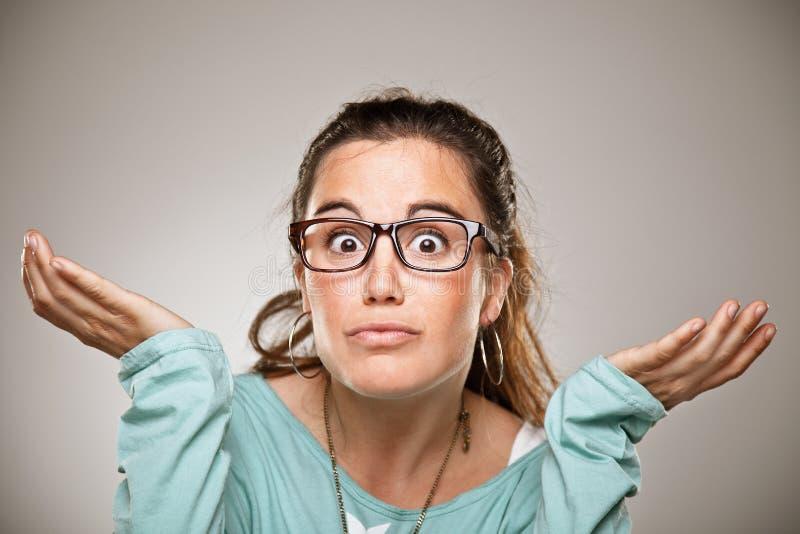 En gesticulant la femme dans le doute faisant l'apparence de haussement d'épaules ouvrez les paumes. photo libre de droits