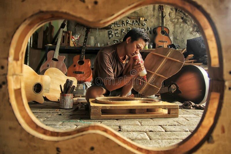 En gitarrhantverkare är upptagen framställning beställningar från hans klienter arkivfoto