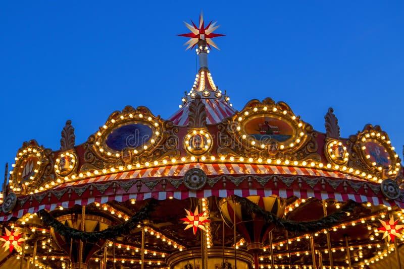 En glödande garnering av karusellen på ett mörker - blå himmel på skymning fotografering för bildbyråer