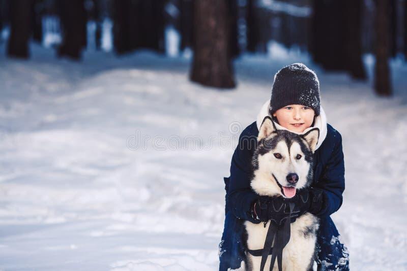 En gladlynt europeisk tonåring kramar en stor hund i vintern i skogen begreppet av vinterferier fotografering för bildbyråer