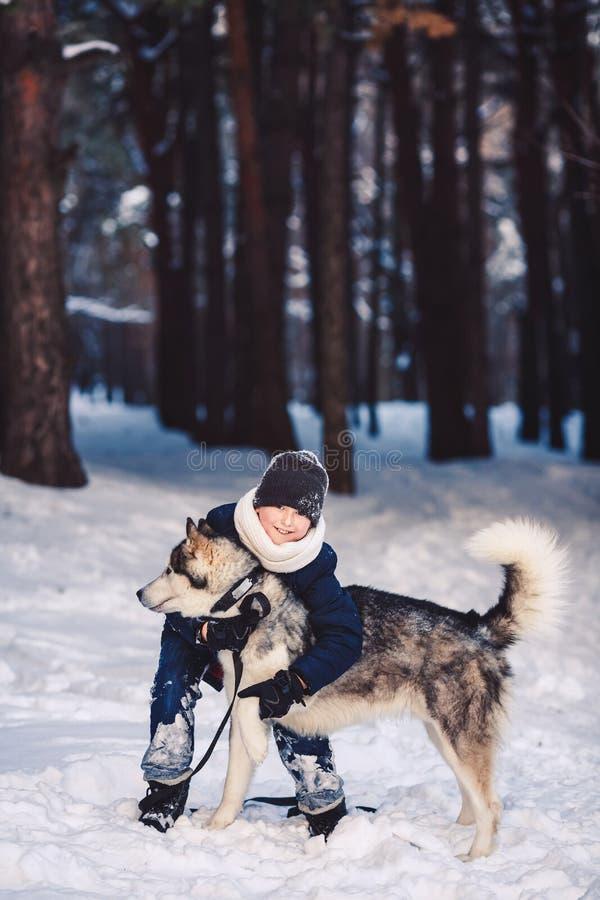 En gladlynt europeisk tonåring kramar en stor hund i vintern i skogen begreppet av vinterferier royaltyfri fotografi