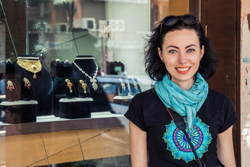 En gladlynt flicka i bakgrunden av en ställa ut med smycken arkivbild