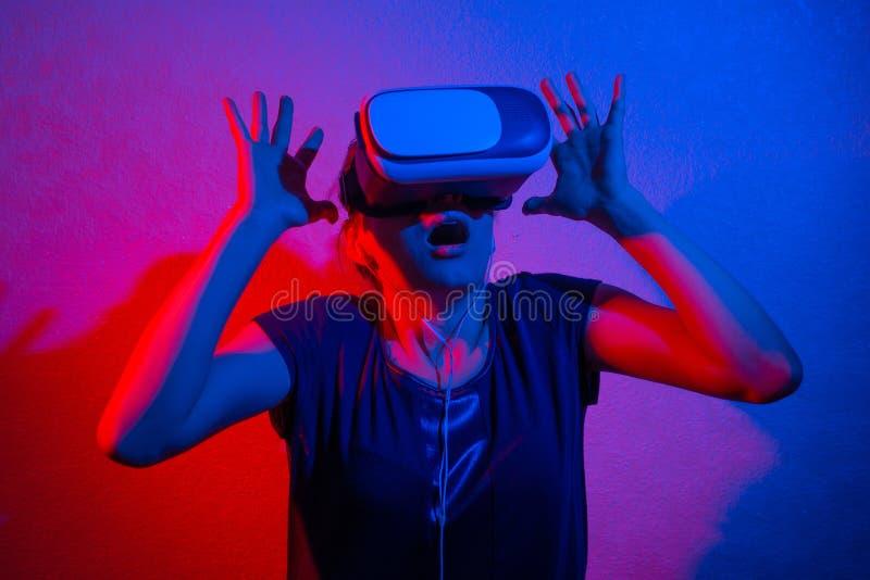 En gladlynt flicka med hennes h?nder upp i virtuell verklighetexponeringsglas arkivfoton