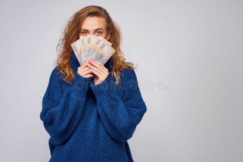 En gladlynt kvinna i en tröja, räkningsdel av framsidan med mone royaltyfri foto