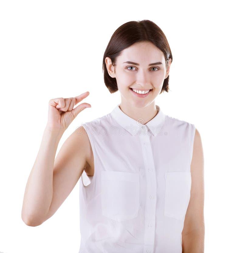 En gladlynt kvinnlig som isoleras på en vit bakgrund En rolig och gullig brunettflicka En damvisning med hennes hand något lite royaltyfri bild