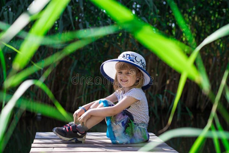 En gladlynt liten flicka i en hatt sitter på flodbanken royaltyfri foto