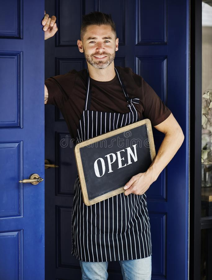 En gladlynt små och medelstora företagägare med det öppna tecknet arkivfoton