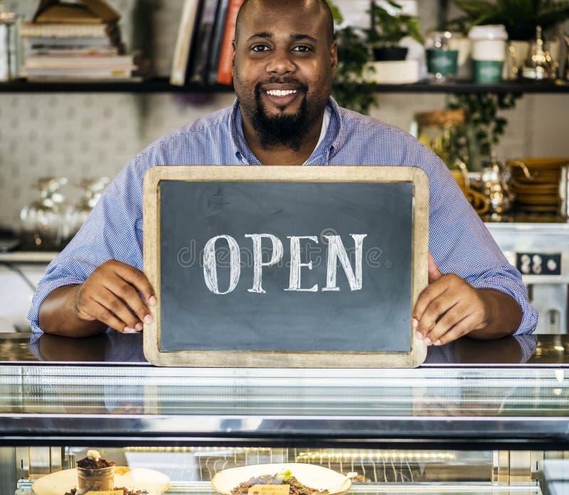 En gladlynt små och medelstora företagägare med det öppna tecknet arkivbild