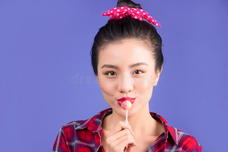 En glamorös flicka äter chupachups, ser in i kameran arkivbild