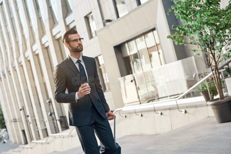 En glasögonprydd ung affärsman klättrar trappan med coffe och resväskan royaltyfri bild