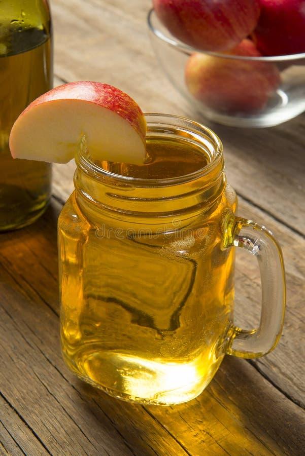 En glasburk med kallt äppelcider på ett gammalt, rustiskt träbord Markerat fokus royaltyfria foton