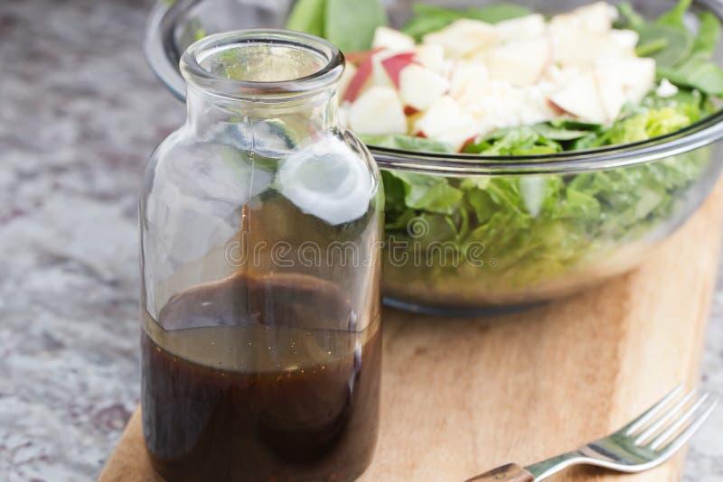 en glasflaska med dressingen som består av balsamic vinäger, honung och olivolja arkivbild