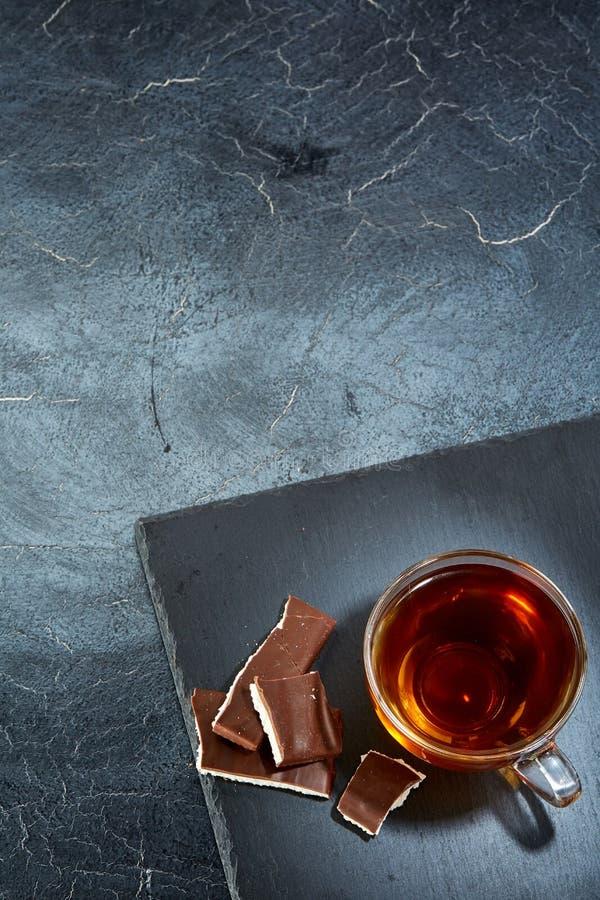 En glass kopp av svart te med choklad på en mörk gråaktig marmorbakgrund, lodlinje Frukostbakgrund royaltyfri fotografi