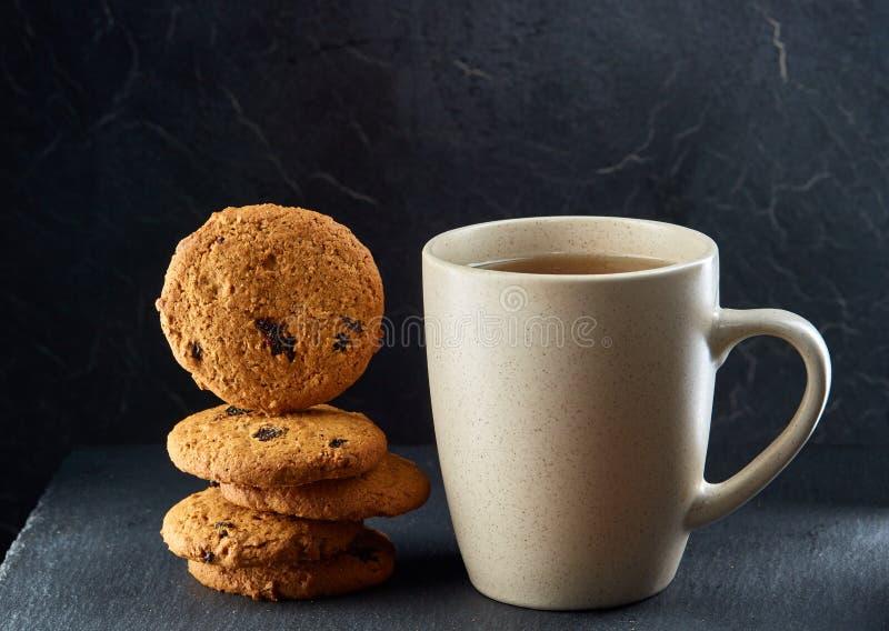 En glass kopp av svart te med kakor på en mörk gråaktig marmorbakgrund Frukostbakgrund arkivbilder