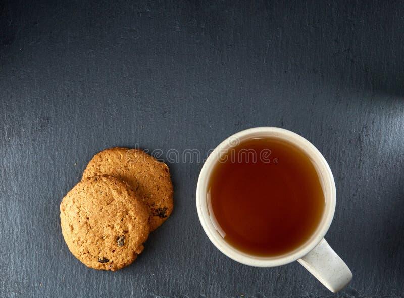 En glass kopp av svart te med kakor på en mörk gråaktig marmorbakgrund Frukostbakgrund arkivfoto
