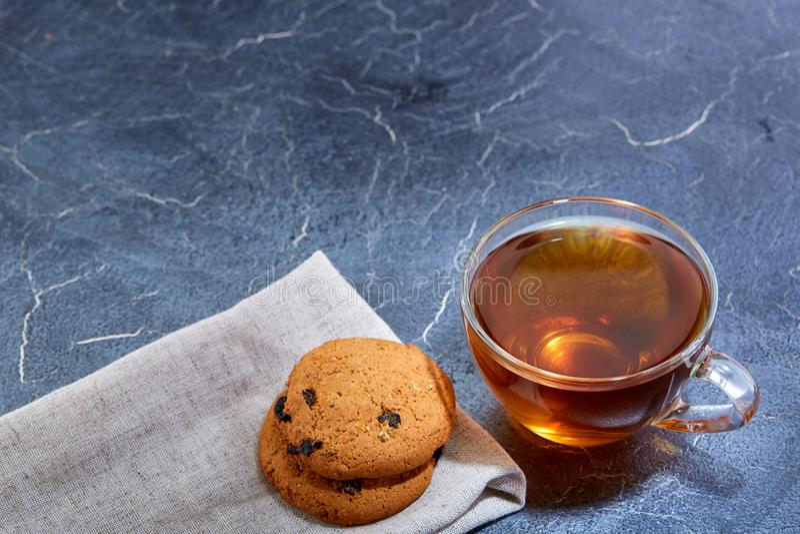 En glass kopp av svart te med kakor på en mörk gråaktig marmorbakgrund, grunt djup av fältet Frukostbakgrund arkivbild