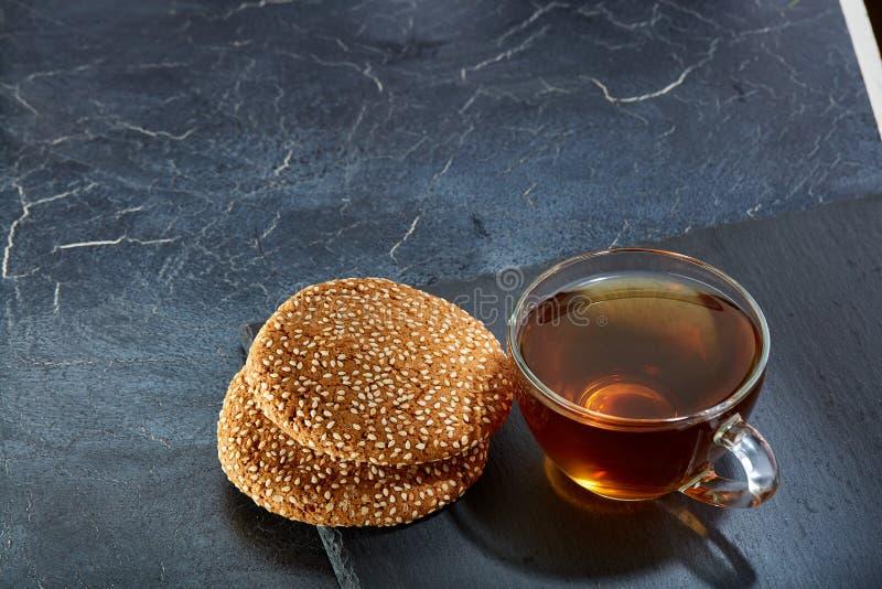En glass kopp av svart te med kakor på en mörk gråaktig marmorbakgrund, grunt djup av fältet Frukostbakgrund arkivbilder