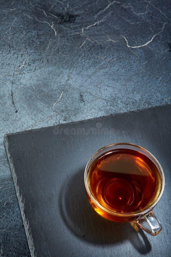 En glass kopp av svart te på en mörk gråaktig marmorbakgrund, lodlinje Frukostbakgrund arkivbilder