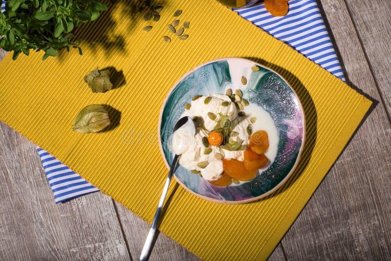 En glass med physalisen och torkade frukter på en platta och på en gul torkduk En drink nära en efterrätt med teskeden arkivfoton