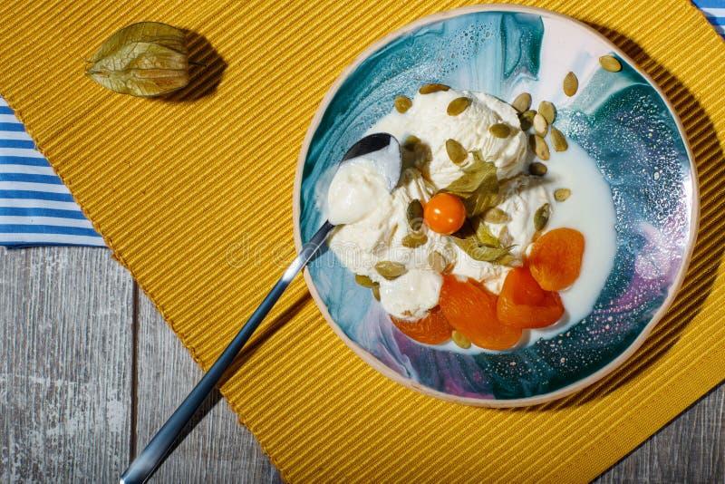 En glass med physalisen och torkade frukter på en platta och på en gul torkduk En drink nära en efterrätt med teskeden royaltyfria foton