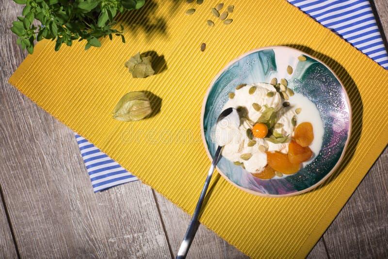En glass med physalisen och torkade frukter på en platta och på en gul torkduk En drink nära en efterrätt med teskeden fotografering för bildbyråer