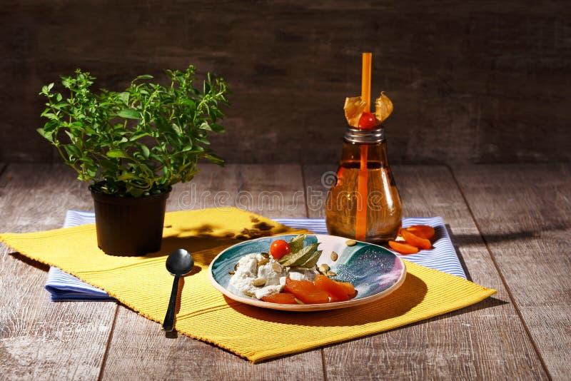 En glass med physalisen och torkade frukter på en platta och på en torkduk En drink nära en glass på en träbakgrund fotografering för bildbyråer