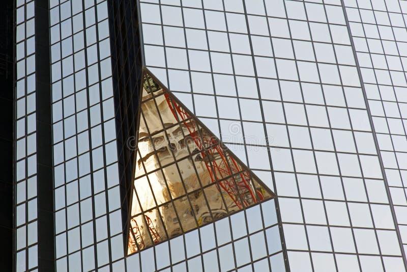 En glass modern byggnad med geometrisk vinklar och reflexion royaltyfri fotografi