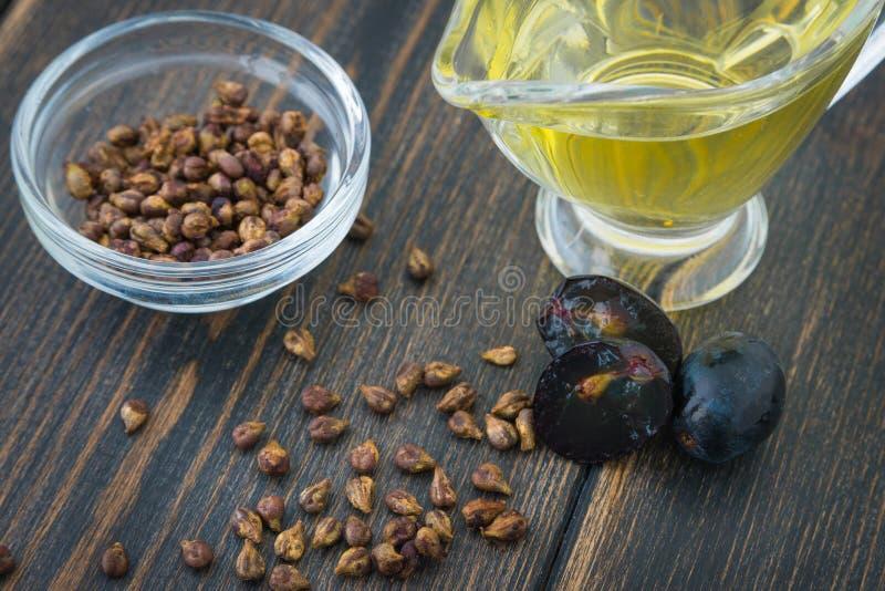 En glass oljekanna av naturlig grapeseedolja, druva-sten olja och gra arkivfoton