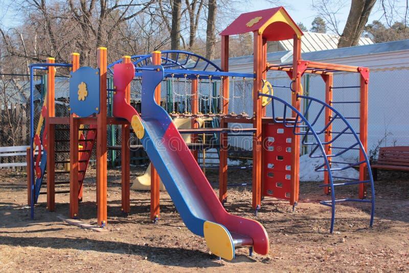 En glidbana för ungarna på lekplatsen på en solig vårdag arkivbilder