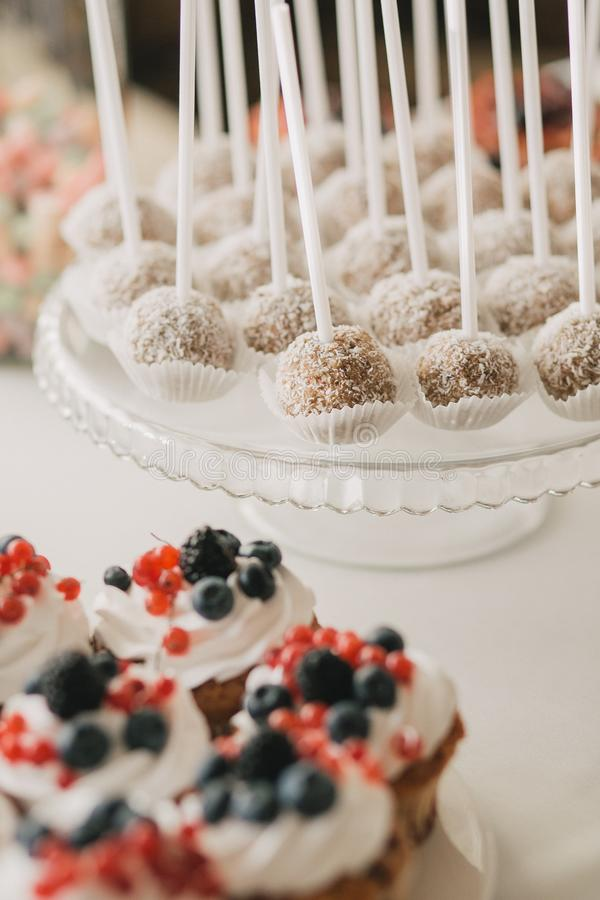 En godisstång med vita plattor muffin dekorerade kräm och bär och en kaka poppar arkivfoto