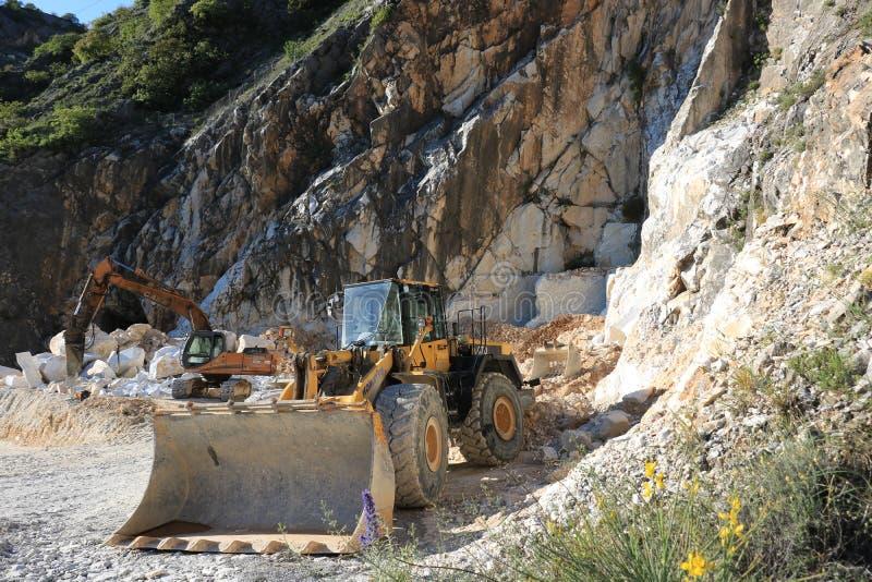 En grävskopa och en bulldozer i en Carrara marmorerar villebrådet Ett stort royaltyfria bilder