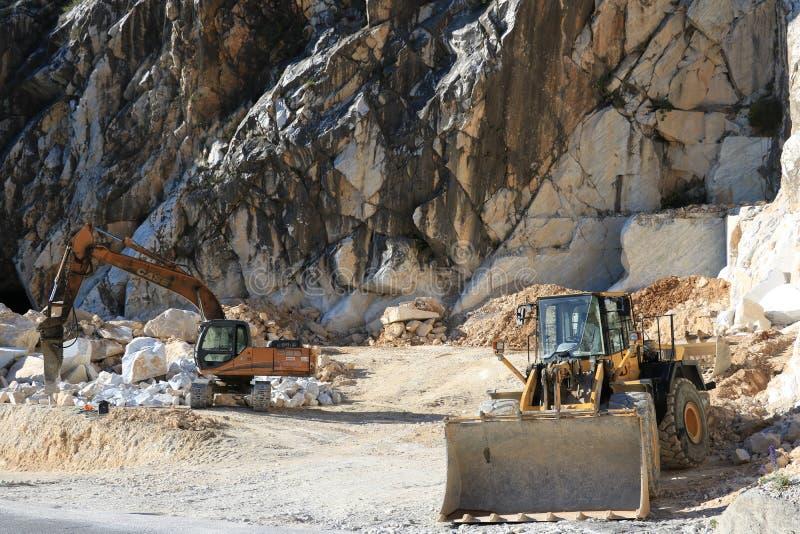 En grävskopa och en bulldozer i en Carrara marmorerar villebrådet Ett stort arkivfoton