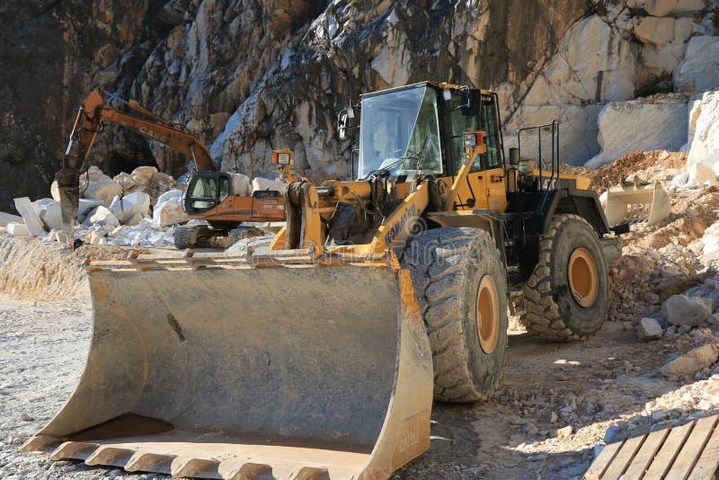 En grävskopa och en bulldozer i en Carrara marmorerar villebrådet Ett stort royaltyfria foton
