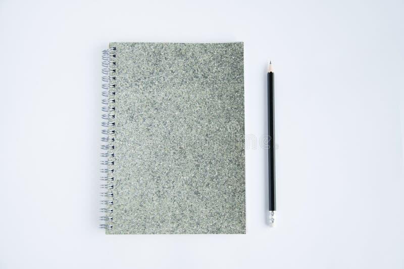 En grå anteckningsbok ligger på tabellen På blocket eller nära den är en svart blyertspenna royaltyfri bild