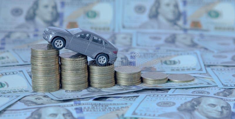 En grå modell av en bil med mynt i form av ett histogram på en dollarbakgrund Begrepp av utlåningen, besparingar, försäkring arkivfoton