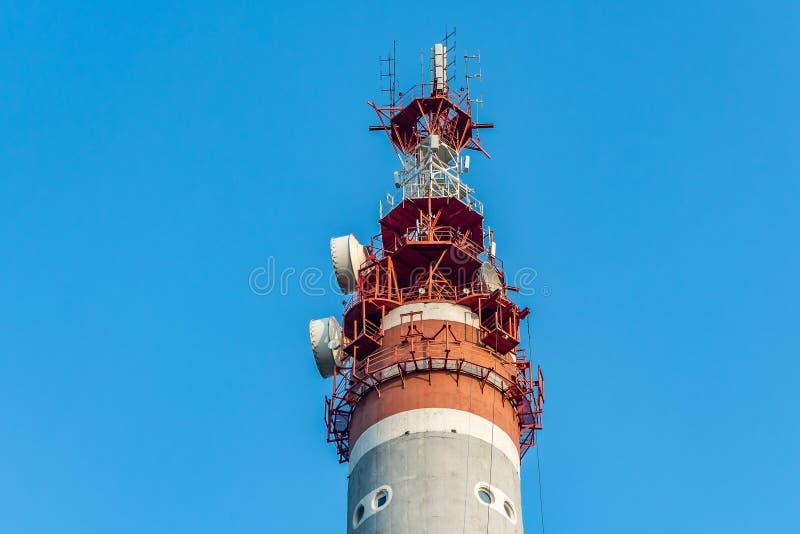 En grått och rött radiorelätorn med gruppen av olika antenner på bakgrunden för blå himmel arkivfoton